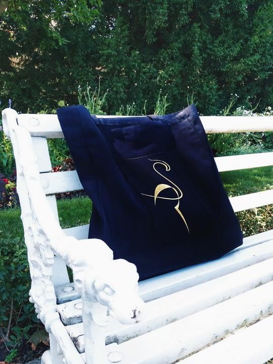 Czarna ekologiczna torba bawełniana z logo flaminga na białej ławce